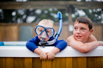 Two boys leaning over the side of a pool