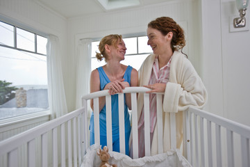 Women standing over bassinet in house