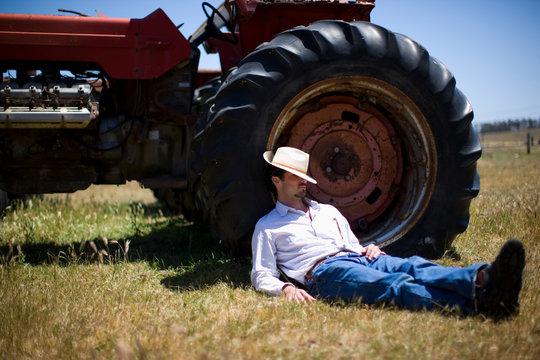 Man asleep against tractor in field