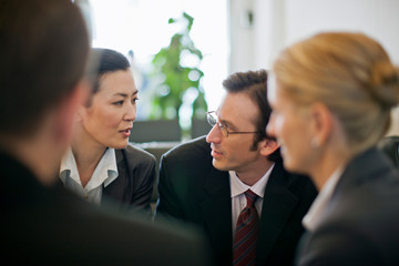 Group of business colleagues conversing in a board room.