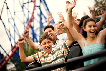 Smiling family riding on a rollercoaster at an amusement park.