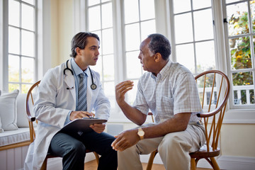 Concerned senior man talking over healthcare options with his family doctor.