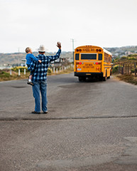 Father and son waving goodbye to school bus