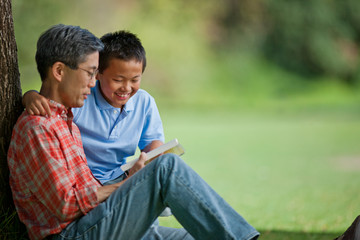 Happy father and son reading a book under a tree.