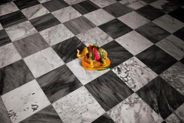 Elephant ornament on tiled floor.