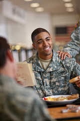 Young soldier smiles happily as he reads a letter over breakfast in the army mess hall.