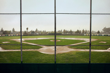 Empty baseball field surrounded by a chain link fence.