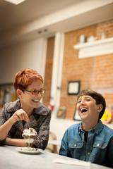 Smiling mother and son enjoying ice cream sundaes.