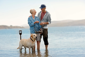 Smiling senior couple standing on a beach together.