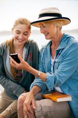 Smiling senior woman and teenage granddaughter looking at a smart phone.