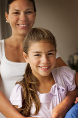 Thirtysomething mother and her daughter smile for a portrait.