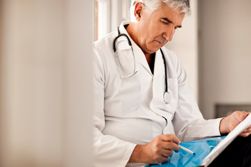 Male doctor reading notes in someones file.