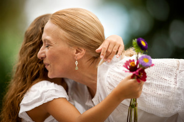 Young girl holding small bunch of flowers as she hugs her grandmother.