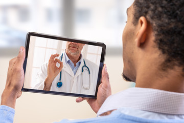 virtual live chat with the patient with digital tablet and a doctor via internet. In-home care for a young male patient in telemedicine or telehealth,