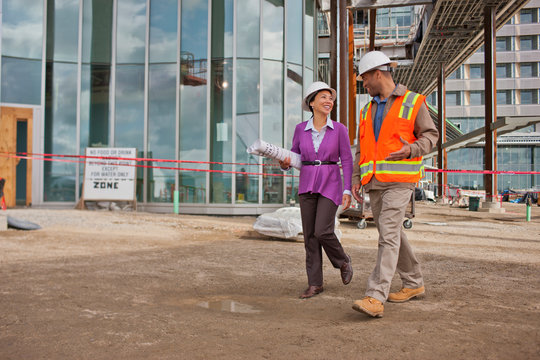 Young female engineer holding the building plans and having a cheerful discussion with the foreman at a construction site.