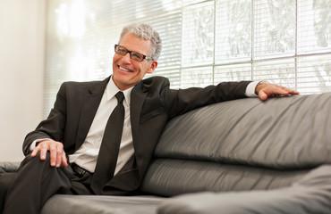 Smiling mature man sitting on a sofa.