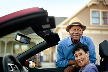 Portrait of happy senior couple with their convertible.