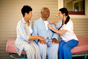 Nurse sitting on the deck of rest-home with elderly patients and listening to their heartbeat with stethoscope.