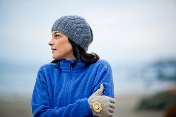 Young woman wearing warm clothing while at the beach in winter.