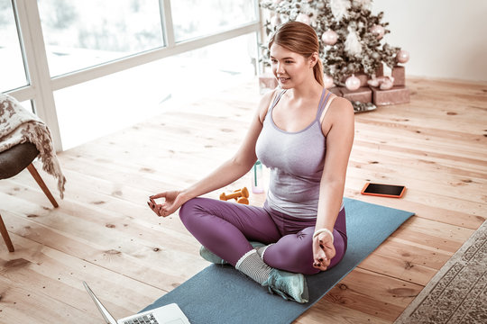 Concentrated good-looking woman having meditation time in front of laptop