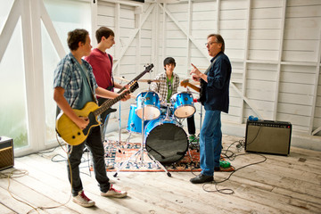 Mid adult man talking to three teenage boys playing with musical instruments inside a garage.