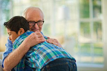 Smiling senior man embracing his young grandson.
