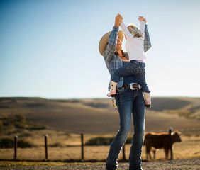Farmer's wife joyfully lifting her toddler into the air while out on the ranch.