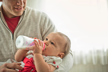 Young father feeding his sweet baby girl with a bottle.