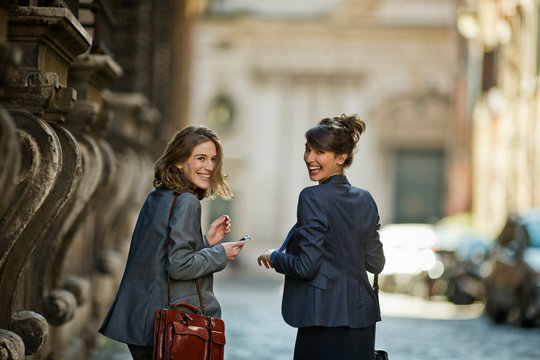 Two laughing young office girls look over their shoulder while heading out in the city.