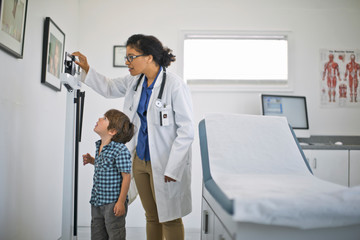 Doctor showing a little boy his height on a ruler.