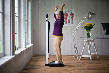 Elderly woman celebrates after stepping on the scales.