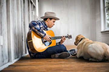 Teenage boy playing an acoustic guitar with his dog.