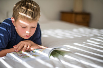Young boy reading in his bedroom.