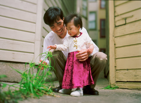 A man and a small girl are admiring a plant outside a house.