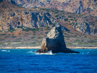 Beautiful mountain and rocky coastline with big rock formation coming out of water