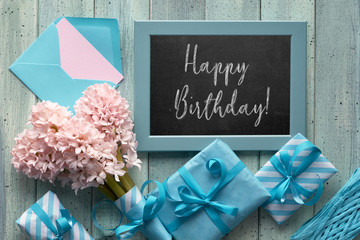 """Chalk board with pink hyacinth and wrapped gift boxes. Flat lay with text """"Happy Birthday""""."""