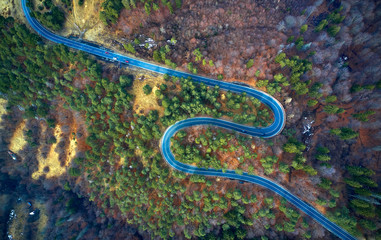 The aerial view of winding road from high mountain pass with trees in Transylvania, Romania, Curved road view by drone in the autumn-winter time