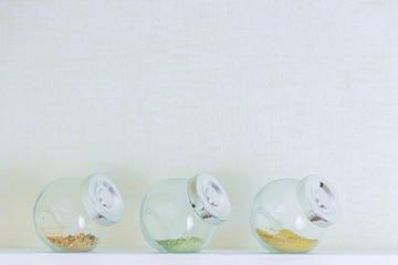 spice in bottles on white wooden shelf. Copyspace.