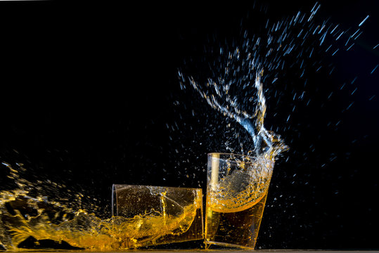 Two golden tequila shots crashing