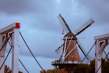Aluminium Prints Swan De Zwaan windmill in Holland Michigan framed by the bridge on a cloudy day