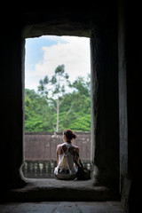 A tourist sitting resting in the ruins at Angkor Wat temple, Siem Reap, Cambodia