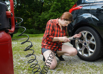 Car checkup in preparation for road trip. Young woman adds air to tire