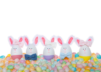 Easter Eggs crafted into bunnies, boys and girls, wearing bow ties and bows on ear sitting in pastel colored speckled jelly beans isolated on white