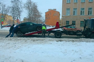 three men load a car on a tow truck during a snowfall
