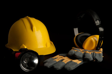 Yellow safety helmet , leather glove, Headphone , head lamp on black background.
