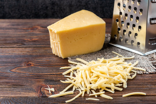 Grated cheese and grater on dark wooden background.