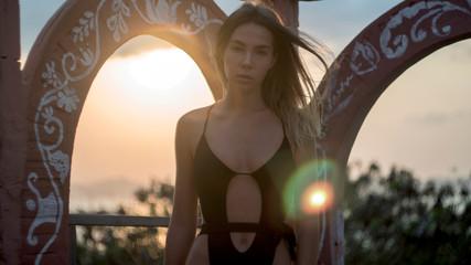model in black bikini against backdrop of setting sun at circular brick arches,