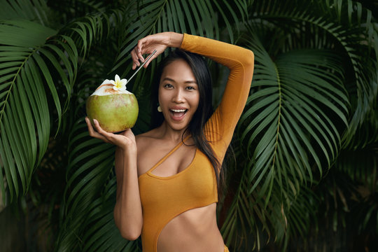 Summer girl in swimsuit with coconut drink at tropical nature