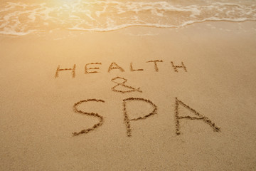 Inscription health and spa on sea sand. Writing in English language on a beach.