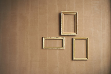 Minimalism. Brown wall with empty gold frames.